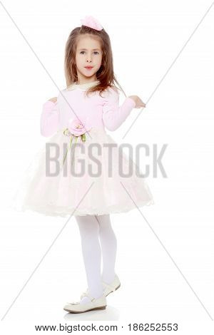 Dressy little girl long blonde hair, beautiful pink dress and a rose in her hair.She spreads her hands aside.Isolated on white background.