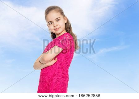 A beautiful little girl of primary school age, with long flowing hair, in a bright red dress.She puts in front of the camera, folded her arms over her chest, and turns to the camera to the side. Close-up.