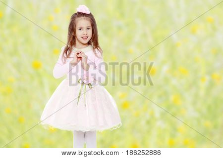Dressy little girl long blonde hair, beautiful pink dress and a rose in her hair.She folded her arms around his chest.Summer white green blurred background.