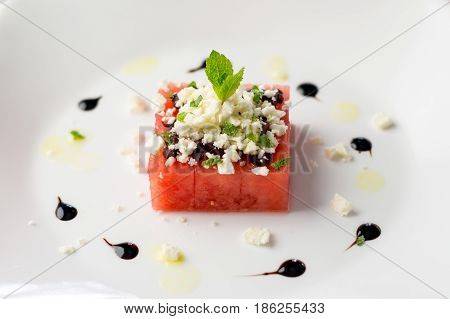Watermelon salad on white. This watermelon cubes salad is made with greek feta cheese crumbs olive slices mint olive oil and balsamic vinegar. So refreshing the perfect food for the summer!
