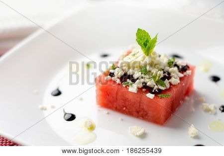Fresh watermelon salad starter. This watermelon cubes salad is made with greek feta cheese crumbs olive slices mint olive oil and balsamic vinegar. So refreshing the perfect food for the summer!