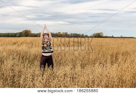 horizontal image of a farmer's caucasian wife standing out in the wheat field in nature and doing yoga stretches in the fall.
