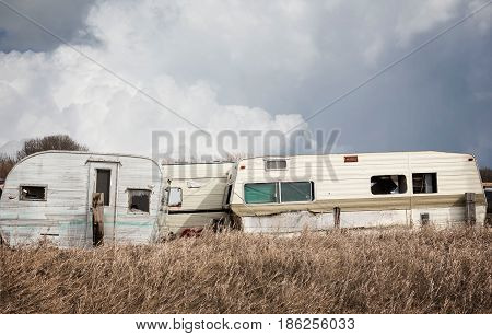 horizontal image of old wrecked holiday campers sitting in the junk yard under a dark cloudy sky in the spring.
