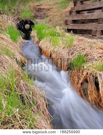 Small creek rushing out of a drainage pipe during spring runoff season