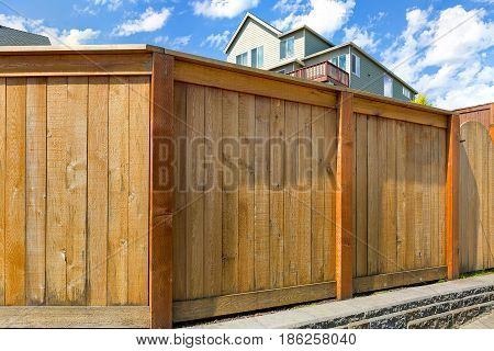 House backyard new wood fence with gate door in suburban residential neighborhood