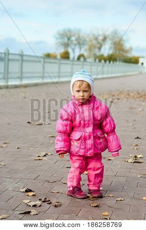 Little Girl In A Jacket Standing Near The Waterfront