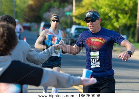 EUGENE, OR - MAY 7, 2017: Volunteers pass out water and sports drink at the 2017 Eugene Marathon race held on the University of Oregon campus.