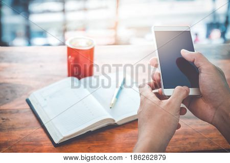 Young businessman hands using mobile smartphone with red coffee cup. Businessmen working at coffee shop (cafe) with mobile smartphone and note book. Vintage color filter.