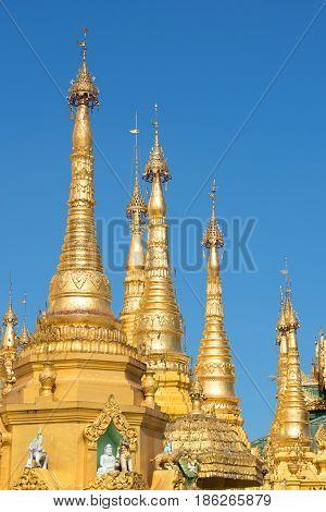 The tops of the golden stupas of the Shwedagon pagoda against the blue sky. Yangon, Myanmar