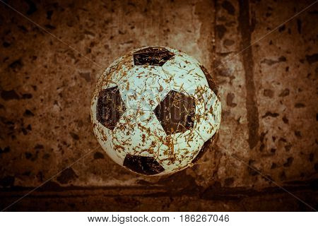 Dirty soccer ball in goal close up.