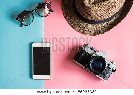 Creative Flat lay fashion style with camera sunglasses smart phone and hat on pastel color background Top view