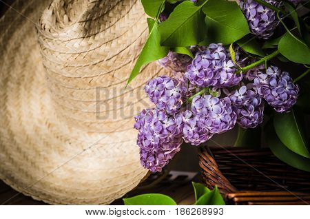 Still-life with a bouquet of lilacs and a straw hat close-up