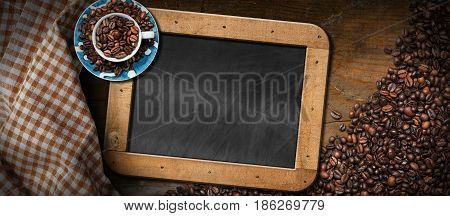 Wooden background with roasted coffee beans empty blackboard with wooden frame a coffee cup and a checkered tablecloth