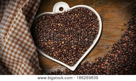 Roasted coffee beans in a heart shaped bowl on a wooden table with a checkered tablecloth. Love Coffee concept