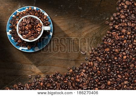 Coffee cup with roasted coffee beans on a dark wooden table with copy space