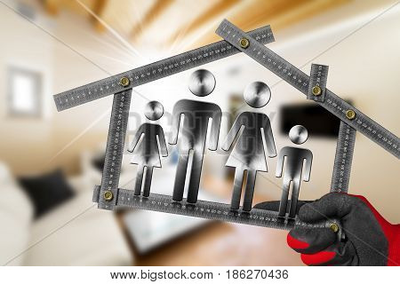 Interior Design Concept - Hand with work glove holding a metal meter ruler in the shape of house with symbol of a family in a living room