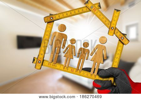 Interior Design Concept - Hand with work glove holding a wooden meter ruler in the shape of house with symbol of a family in a living room