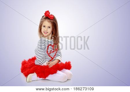 Portrait of a little girl in a bright red skirt with a red bow on his head.The girl sat on his lap.Purple gradient background.