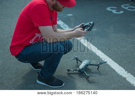The guy starts a quadrocopter with an asphalt surface. Preparation for start, calibration of navigation systems