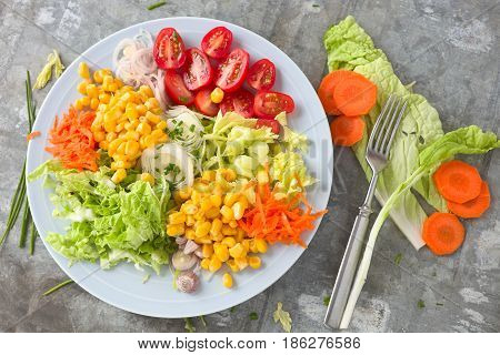 Chopped vegetable salad with corn, leek, carrot, tomato and lettuce.