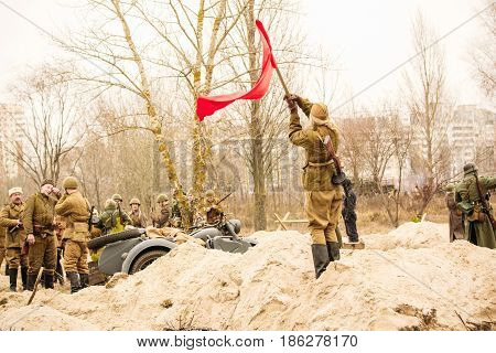 Gomel, Belarus - November 26, 2016: A girl of a Red Army soldier waving a flag in honor of victory. Reconstruction of the battle for Gomel