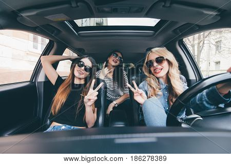 Group Of Friends Having Fun On The Car. Singing And Laughing In The Car Drive In City Center
