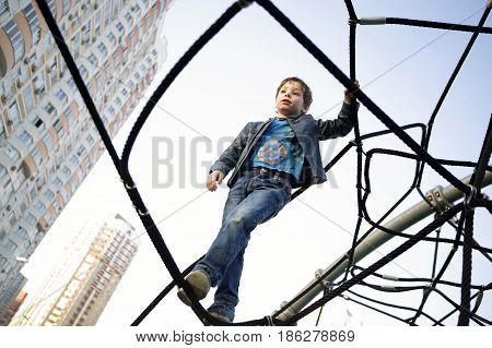 Boy At Playground Climbing Net