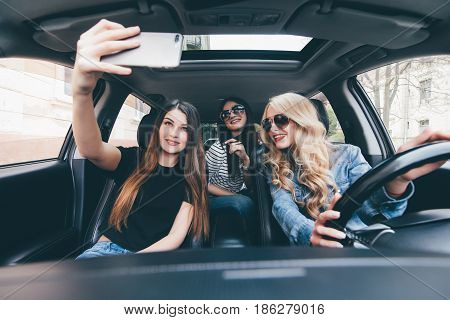 Beautiful Stylish Girls Are Making Selfie, Looking At Camera Having Fun While Sitting In The Car