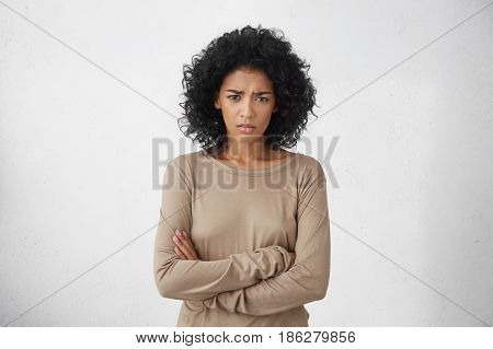 Angry Annoyed Young Housewife Keeping Arms Crossed And Staring At Camera With Sceptical And Distrust