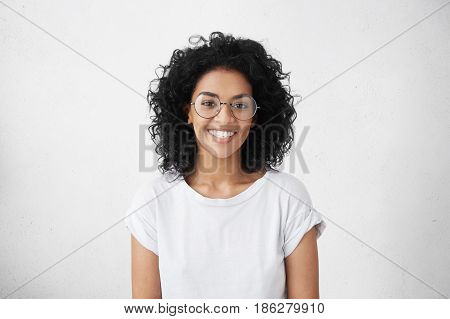 Indoor Portrait Of Beautiful Brunette Young Dark-skinned Woman With Shaggy Hairstyle Smiling Cheerfu
