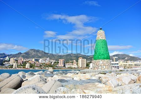A View To Mediterranean Sea, A Lighthouse With Breakwaters And Hotels At The Background From A Pier