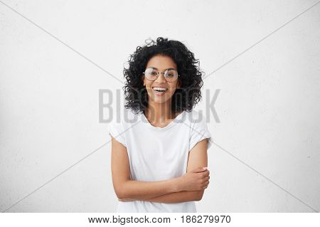 Indoor Portrait Of Beautiful Young Dark-skinned Woman Wearing Big Round Eyeglasses And Casual White