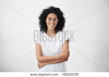 Beautiful Inexperienced Fledgling Young Dark-skinned Female Singer Standing At White Studio Wall Wit
