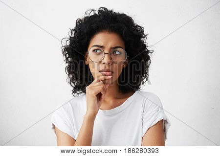 Isolated Portrait Of Stylish Young Mixed Race Woman With Dark Shaggy Hair Touching Her Chin And Look