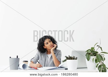Looking For Inspiration And Muse. Attractive Young Pensive Woman Engineer Wearing Grey Shirt Over Wh