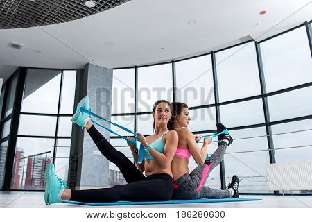Two female friends working out together in gym sitting on mat back to back stretching leg muscles with elastic band.
