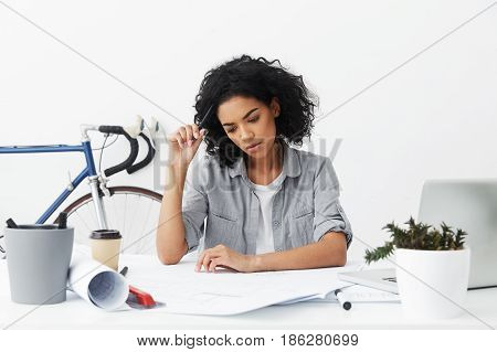 Candid Shot Of Serious Young Dark-skinned Female Architect Feeling Frustrated And Worried While Noti