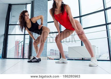 Sexy young women wearing leotards and trainers dancing modern standing in tempting positions indoors.