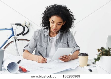 Beautiful Cheerful Young Dark-skinned Female Architect Making Drawings Sitting At Her Workplace With