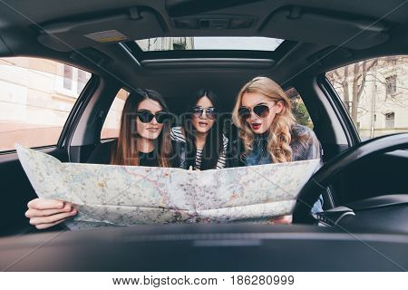 View Of Three Beautiful Young Cheerful Women Looking Away With Smile While Sitting In Car