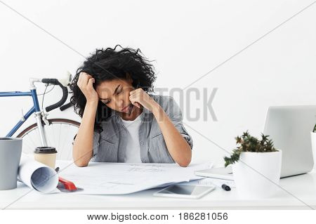 Portrait Of Bored And Tired Afro American Female Architect Working On Architectural Plan Unwillingly