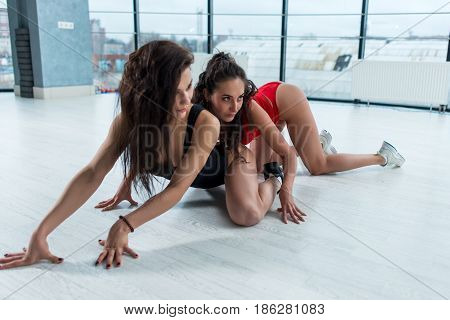 Two sexy brunette women wearing swimsuits posing in seductive position standing on hands and knees crawling on floor indoors