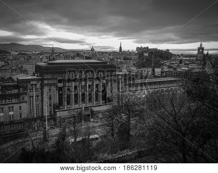 Black and white image of Edinburgh city on dark sky with black clouds view from Calton Hill Scotland UK