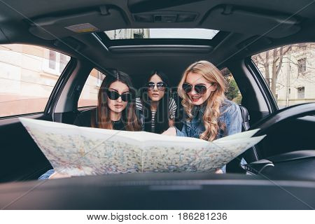 View Of Three Beautiful Young Cheerful Women Try To Find Road In The Maps While Sitting In Car