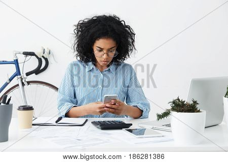 People And Modern Technologies Concept. Concentrated Young Mixed Race Female Secretary Reading Urgen