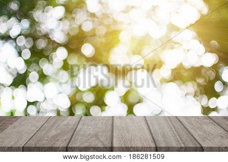 Empty wooden table top and sunny blurred bokeh background for product display