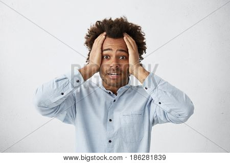 Indoor Shot Of Frightened Young Dark-skinned Man Keeping Hands On His Head, Raising Eyebrows, Having