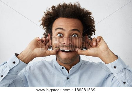 Funny Goofy Young Dark-skinned Man Grimacing Stretching Mouth With Both Hands And Making Ears Stick