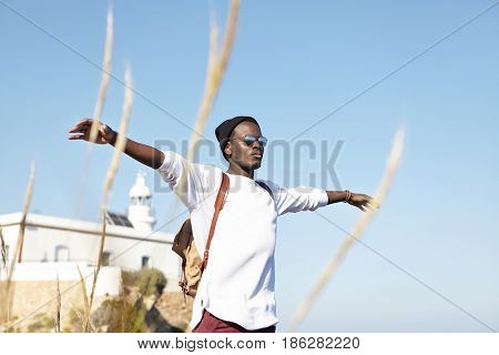 Outdoor Shot Of Attractive Stylish Black Traveler With Backpack On Shoulders, Spreading His Arms Fee