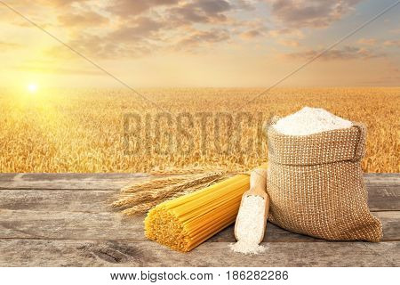 uncooked pasta from durum wheat, wholegrain flour in bag and scoop on table with ripe cereal field on the background. Golden wheat field on sunset. Photo with place for text